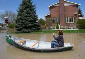 A resident canoes down a flooded street in Saint-Jean-sur-Richelieu, May 6, 2011.