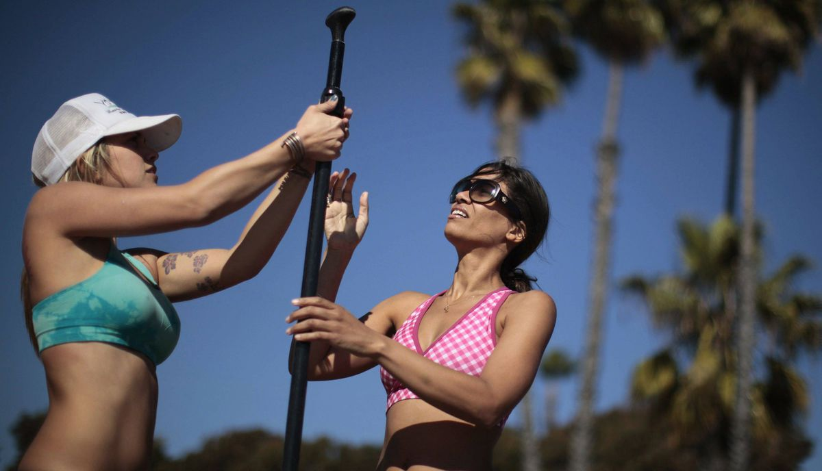 Instructor Sarah Tiefenthaler (L) adjusts a paddle for Chelsea McElroy, 40, during her Yogaqua class, which combines yoga and paddleboarding, in Marina Del Rey, Los Angeles January 28, 2012.