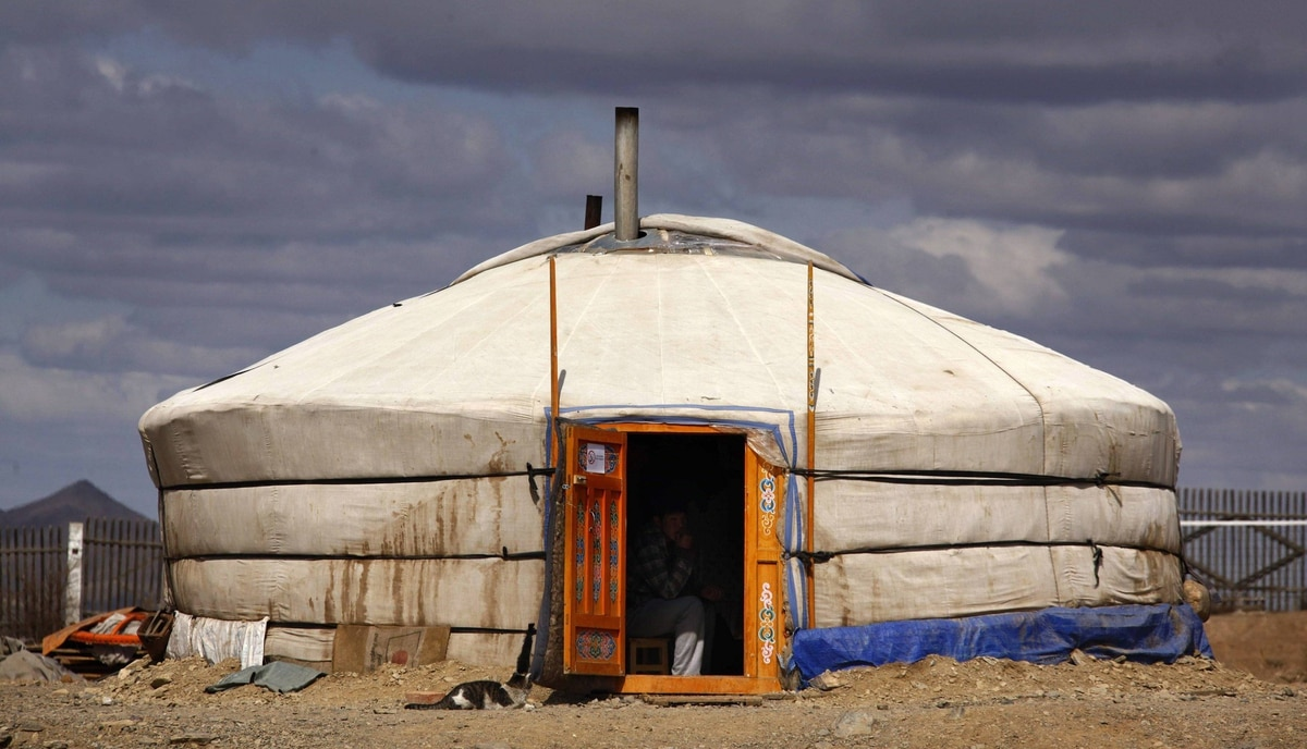 """A small-scale miner sits in a traditional Mongolian tent located at a mining camp around 250km south-west of the Mongolian capital city Ulan Bator. In the last five years, dwindling legal gold supplies and a spike in black market demand from China have made work much more lucrative for Mongolia's """"ninja miners"""" - so named because of the large green pans carried on their backs that look like turtle shells."""