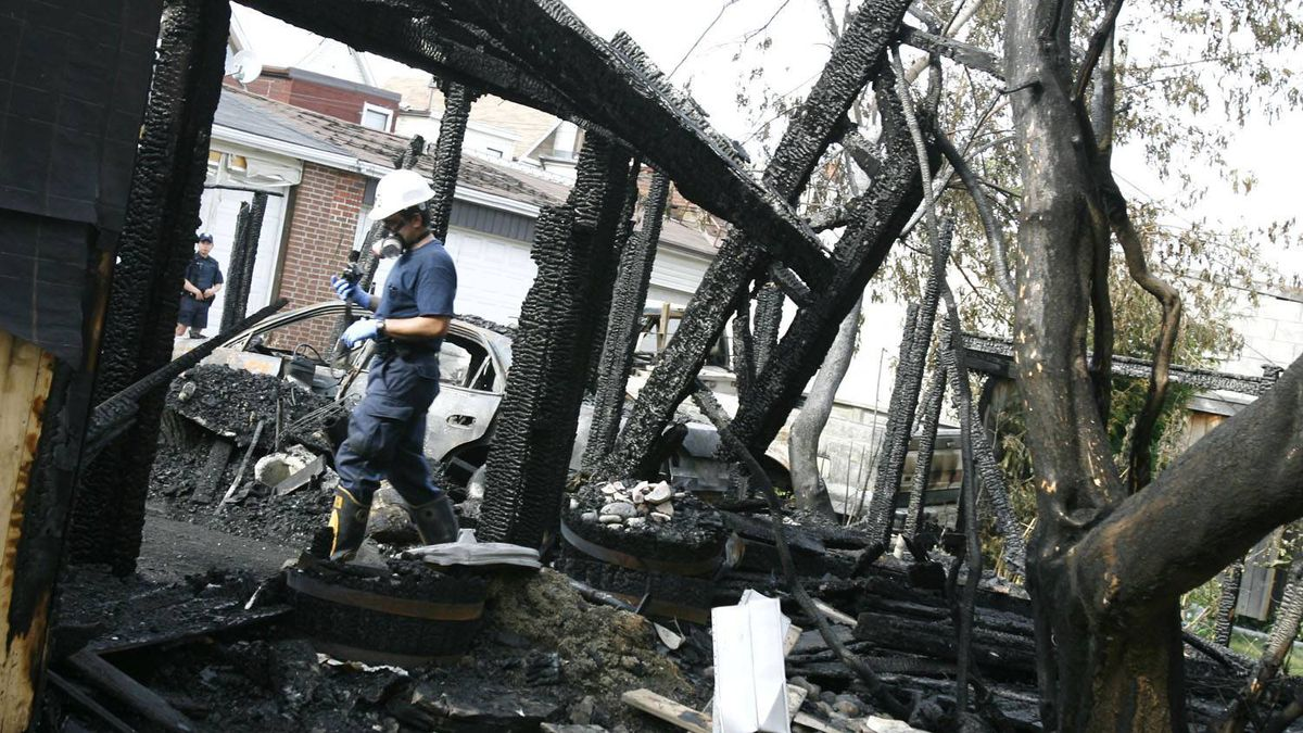 An investigator collects evidence at the scene of a fire near Dupont and Shaw Streets in July, 2007.