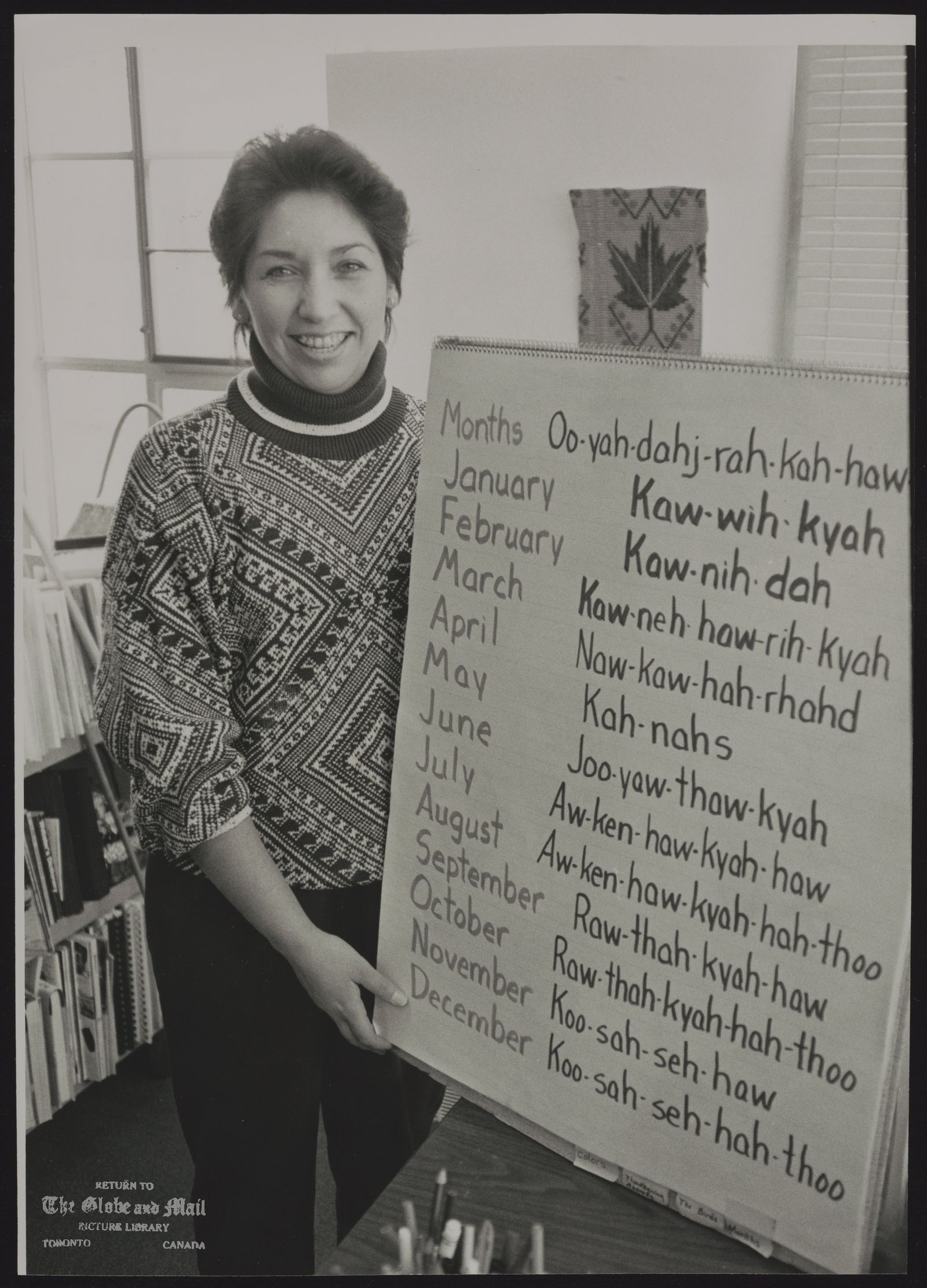 NATIVE PEOPLE CANADA MISCELLANEOUS TUSCARORA TEACHER BETSY BISSELL, DISPLAYS PRONUNCIATION CHART FOR THE IROQUOIS CONFEDERACY LANGUAGE.