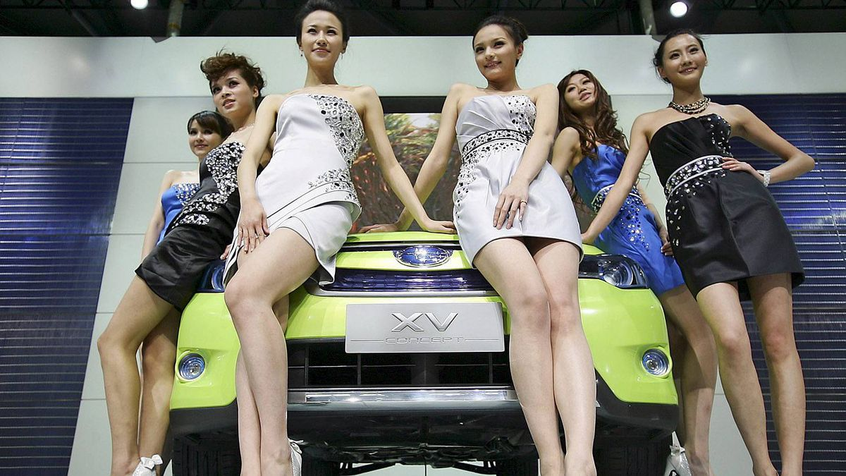 Models sit on a Subaru's XV concept car to pose for photographers at Subaru presentation section on the press day at the Shanghai International Auto Show Tuesday, April 19, 2011 in Shanghai, China. (AP Photo)