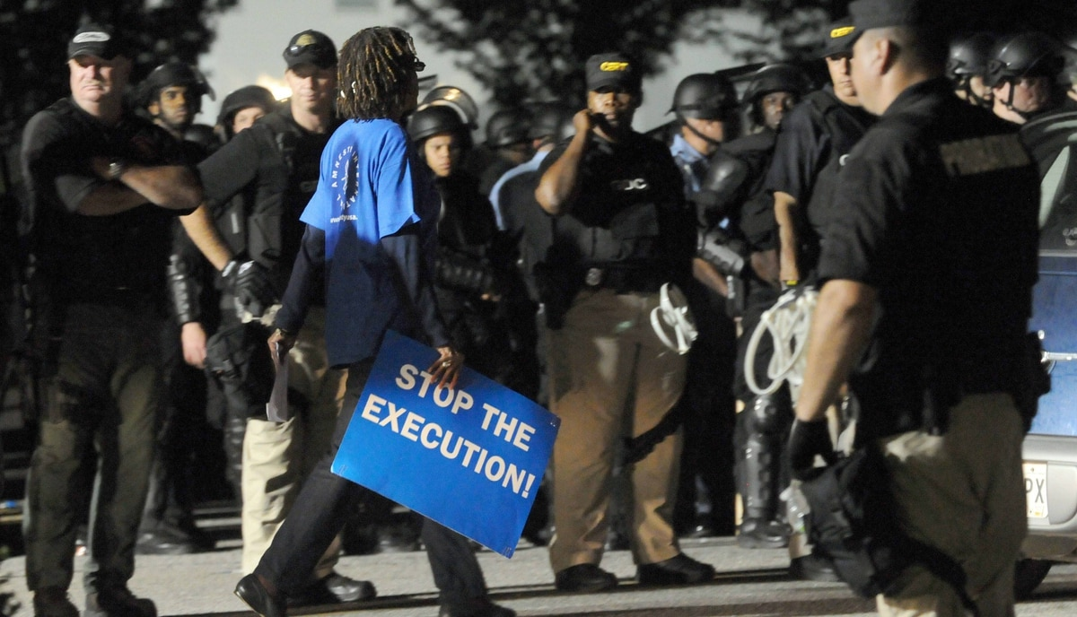 A demonstrator walks between a phalanx of riot-geared police after the execution of convicted cop killer Troy Davis at the Georgia Diagnostic and Classification Prison in Jackson, Georgia. Davis died for the 1989 murder of a Savannah police officer, although his supporters contend several witnesses had recanted their trial statements.