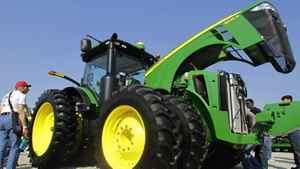 In an Aug. 31, 2011 photo people examine John Deere farming equipment on display during the Farm Progress Show in Decatur, Ill.