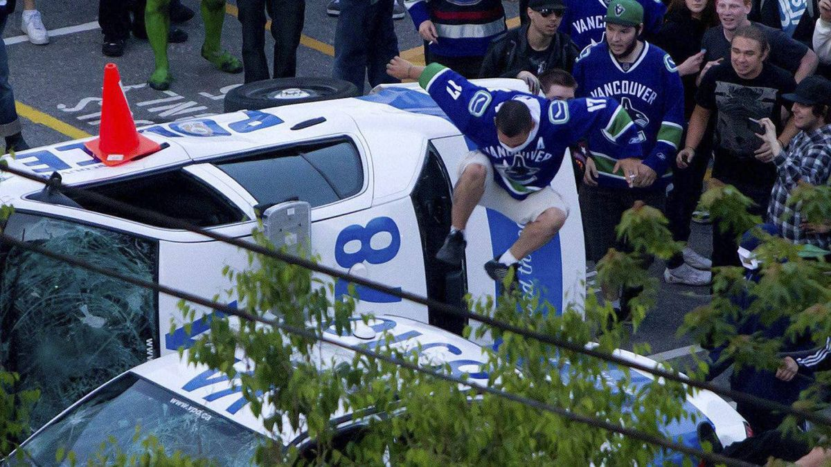 A Vancouver Canucks fan jumps from a police car that was overturned by rioters following the Vancouver Canucks defeat by the Boston Bruins in the NHL Stanley Cup Final in Vancouver, June 15, 2011.