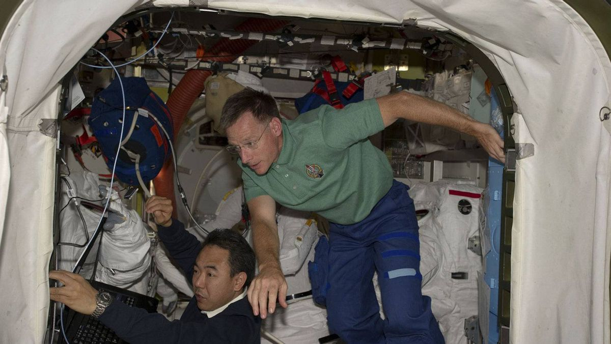 Space shuttle Atlantis Commander Chris Ferguson (R) and Japan Aerospace Exploration Agency (JAXA) astronaut Satoshi Furukawa (L) work in the International Space Station's Quest airlock inspecting space suits in this photo provided by NASA and taken July 12, 2011.