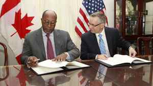 U.S. Trade Representative Ron Kirk, left, and Trade Minister Ed Fast sign the Softwood Lumber Extension Agreement in Washington in Januarty.