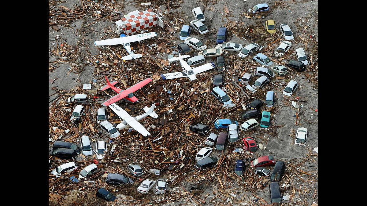 Cars and airplanes swept by a tsunami are pictured among debris at Sendai Airport, northeastern Japan