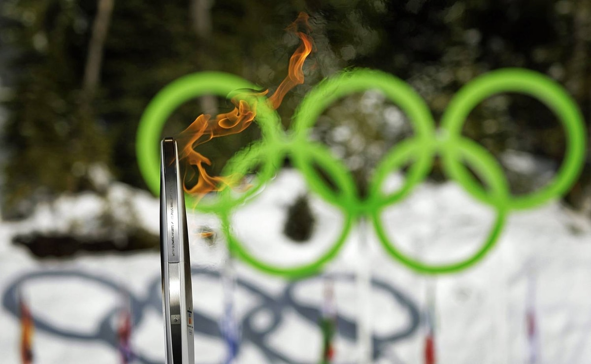 The Olympic torch is seen next to the Olympic rings as it arrives at the biathlon track in Whistler, B.C., on Friday, Feb. 5, 2010.
