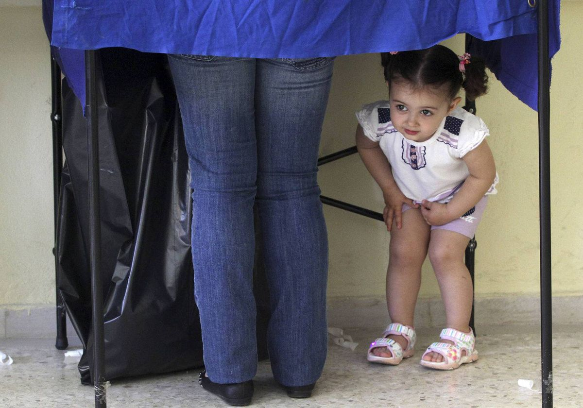 A girl peers under a polling booth while her mother prepares to vote at a polling station in Athens during Greece's general election May 6, 2012.