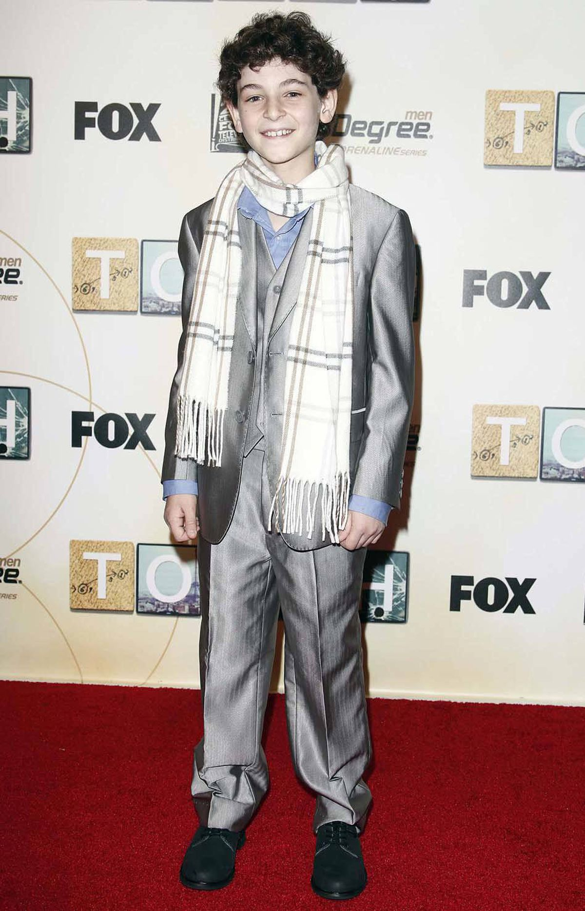 "Gladly. Child actor David Mazouz, star of the new Fox series ""Touch,"" attends the show's premiere in New York on Sunday in a natty silver suit and a rakish scarf."