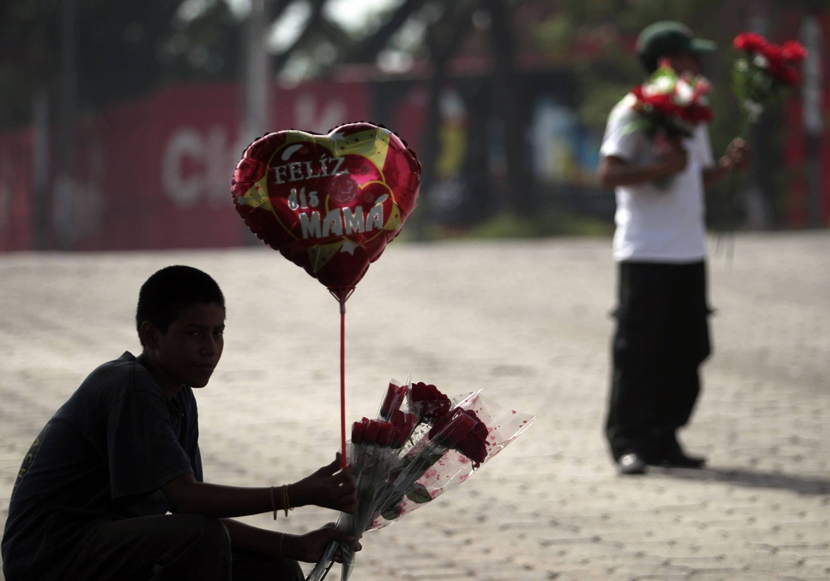Teenagers sell flowers and balloons on the street on Mother's Day in Managua.