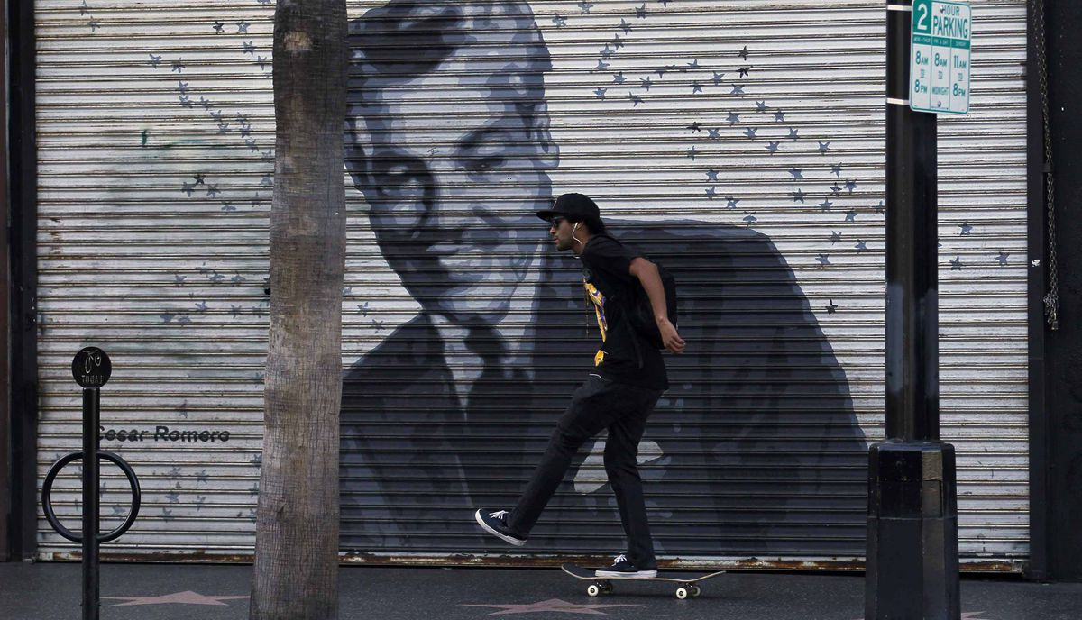 A skateboarder pushes past a closed store front along Hollywood Boulevard in Hollywood, California February 22, 2012.