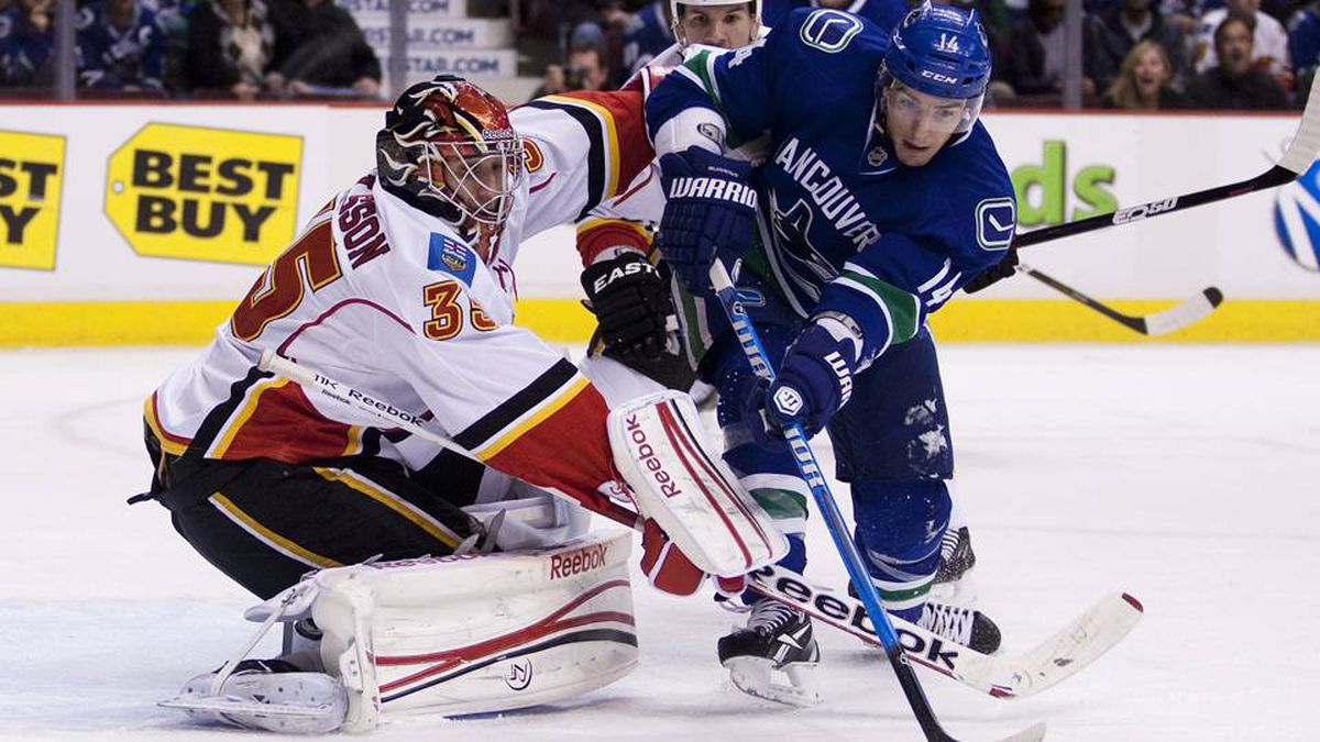 Vancouver Canucks' Alex Burrows (R) is stopped by Calgary Flames goaltender Henrik Karlsson during the first period their NHL game in Vancouver.