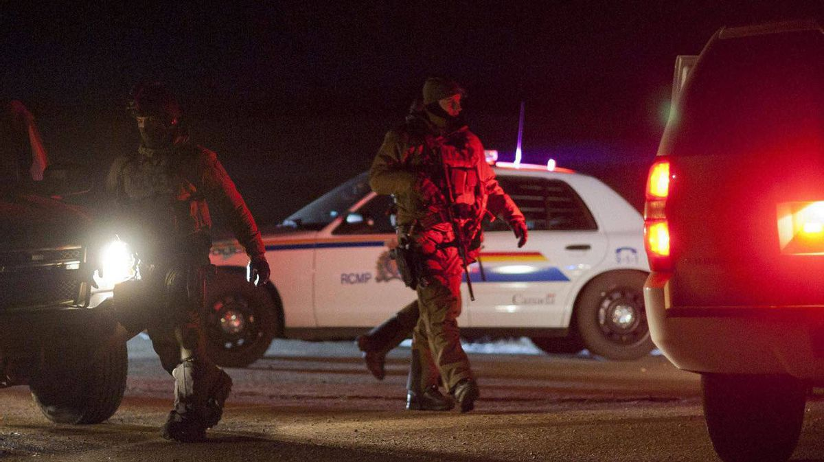 RCMP tactical team members depart from a road block north of the scene where two RCMP officers were involved in a shooting, east of Sedgewick, Alta., on Feb. 7, 2012.