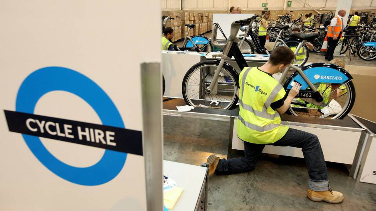 Workers in London attach branding stickers and signs to bicycles for London's new rent-a-bike program.