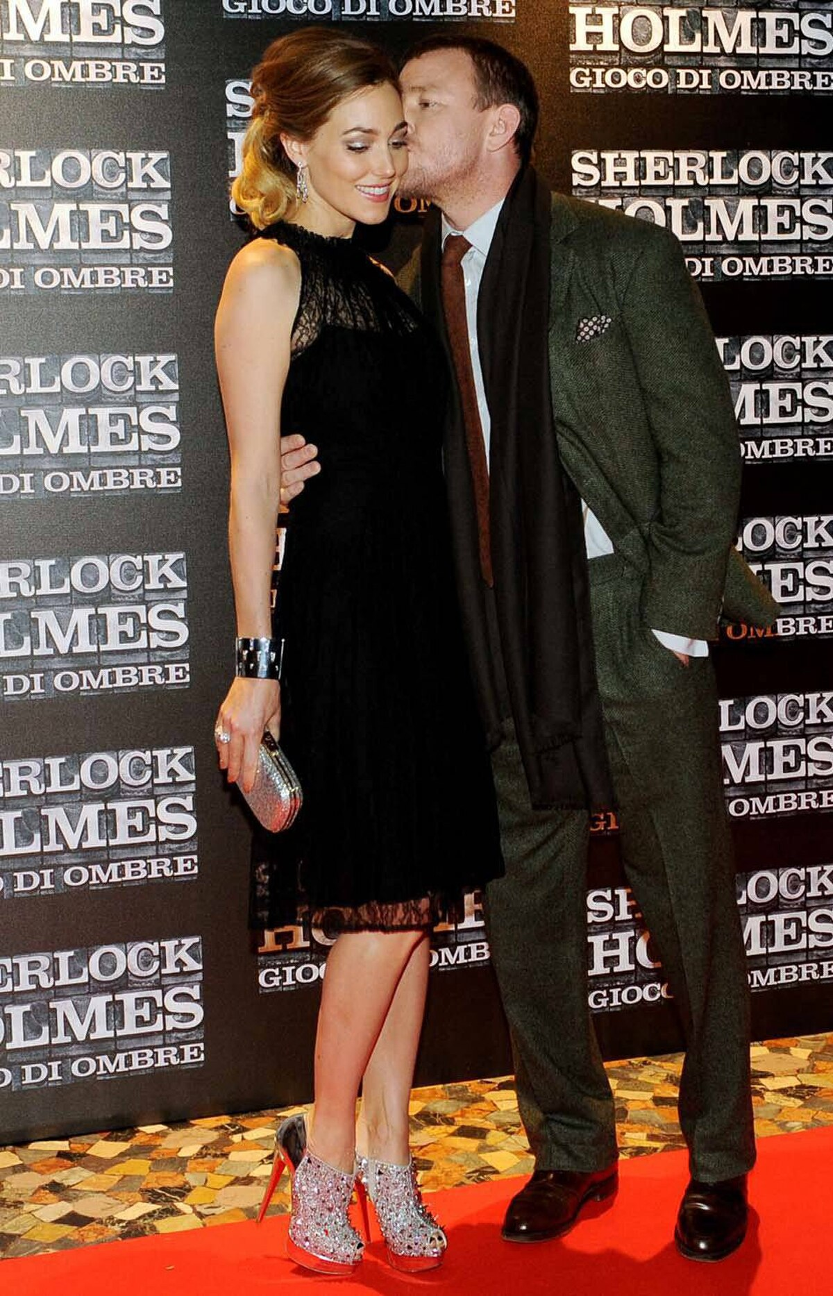 """Guy Ritchie kisses his younger, softer partner Jacqui Ainsley at the premiere of """"Sherlock Holmes 2: A Game of Shadows"""" in Rome on Sunday."""