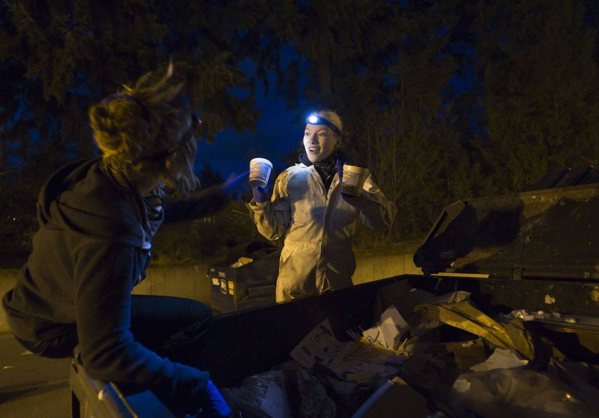 Anna-Rae Douglass (L), 23, and Robin Pickell, practising 'freegans', react to finding food in a dumpster behind an organic grocery store in Coquitlam.