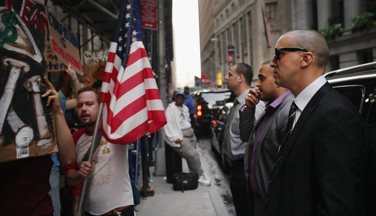 """Businessmen look at demonstrators opposed to corporate profits on Wall Street march in the Financial District on September 26, 2011 New York City. Hundreds of activists affiliated with the """"Occupy Wall Street"""" demonstrations have begun living in a park in the Financial District near Wall Street."""
