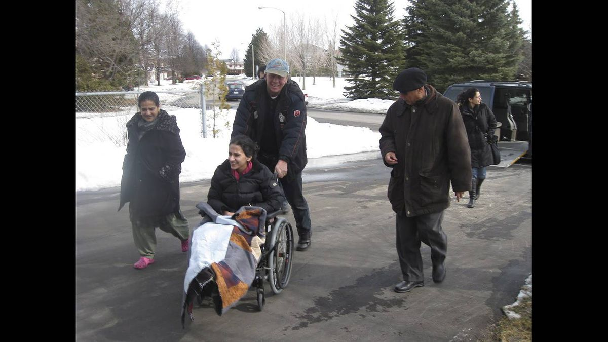 Bushra Saeed, pushed by a taxi driver and flanked by her mother Neelam and father Amjad, makes a first brief visit home in Orleans, Ont., on Feb. 28, 2010. Her sister Hanaa is in the background.