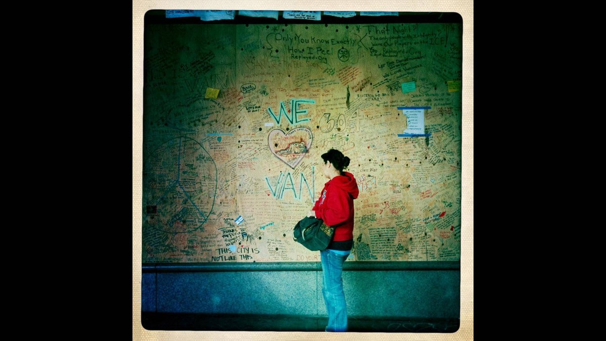 A woman stops to read the messages written on plywood covering broken windows of the Hudson's Bay Company after last week's riot in Vancouver, British Columbia, Sunday, June 19, 2011.