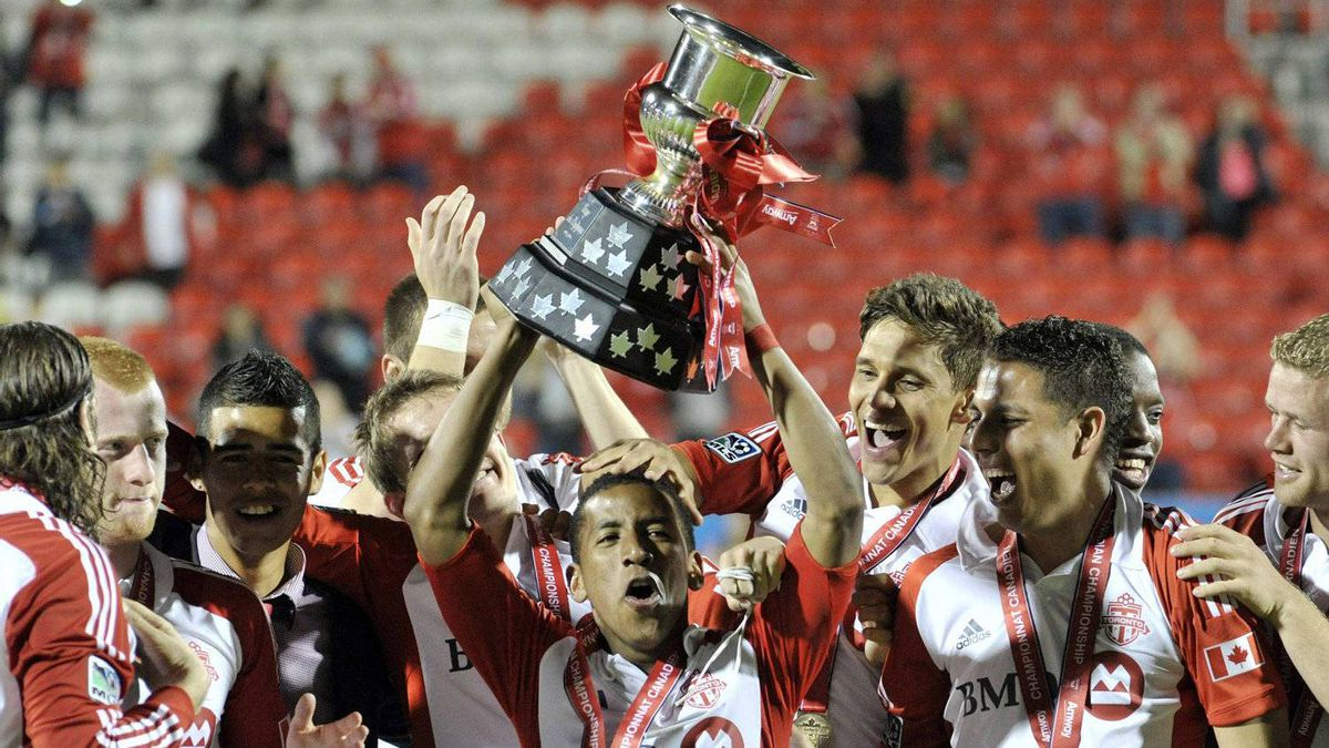 Toronto FC's Joao Plata holds the winners trophy after defeating the Vancouver Whitecaps in their 2012 Canadian Championship final soccer match in Toronto May 23, 2012.