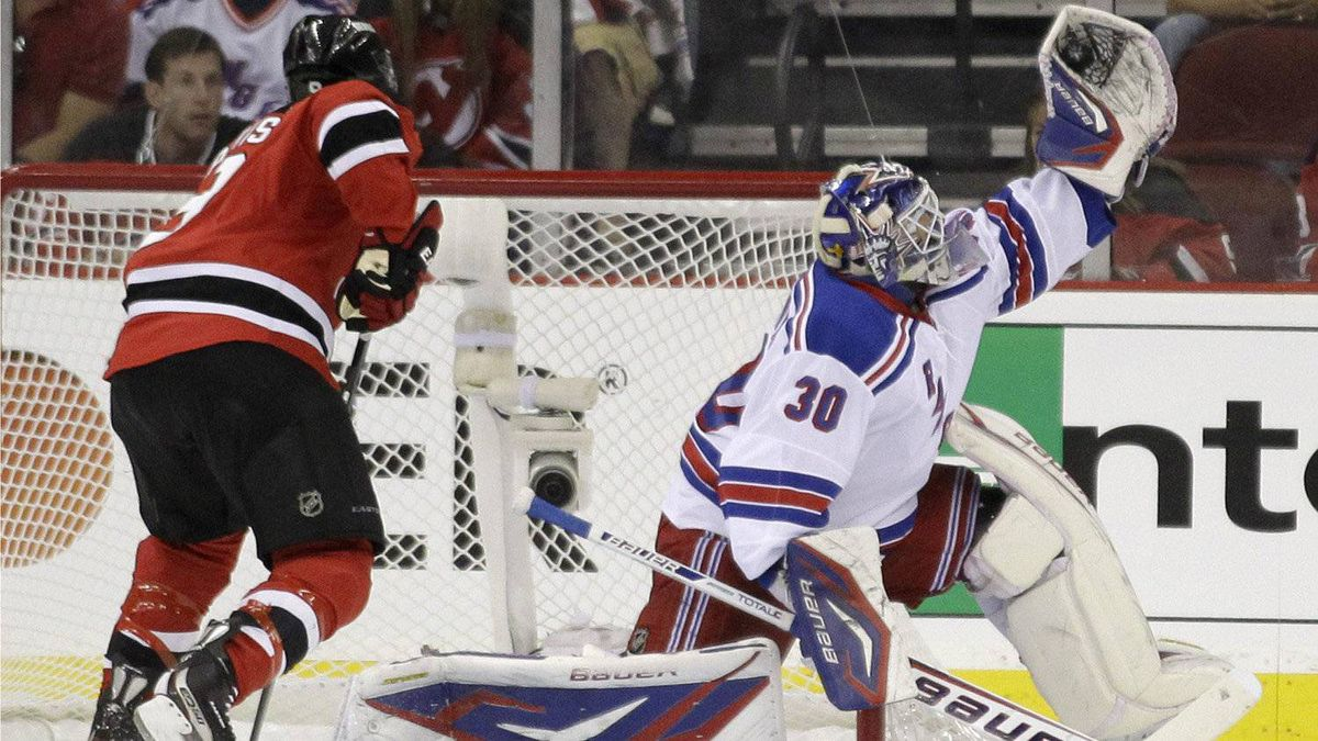 New York Rangers goalie Henrik Lundqvist, right, of Sweden, stops a shot as New Jersey Devils right wing Dainius Zubrus, of Lithuania, looks for a rebound during the first period of Game 3 of the NHL Stanley Cup Eastern Conference final, Saturday, May 19, 2012, in Newark, N.J.