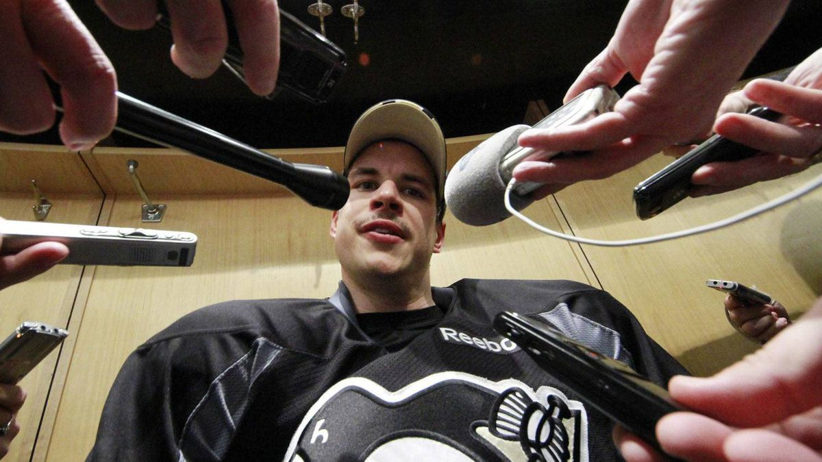 Pittsburgh Penguins' Sidney Crosby is surrounded by reporters at his locker after participating in a game day morning skate in preparation for his return to NHL hockey action against the New York Islanders, in Pittsburgh, Monday, Nov. 21, 2011. (AP Photo/Gene J. Puskar)