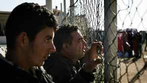 Tunisian immigrants wait to be transfered to a temporary facility after their arrival on the Italian island of Lampedusa on February 13, 2011. Italy said the same day it was planning to deploy its security forces in Tunisia to stop a wave of immigrant arrivals, as coastguards intercepted another 1,000 immigrants from the North African state