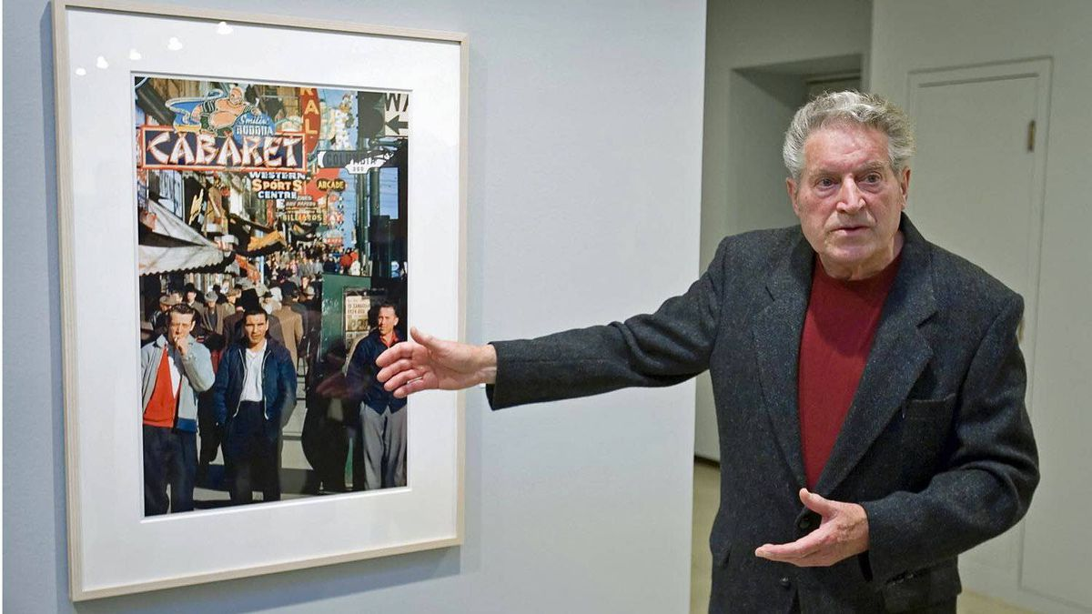 Vancouver photographer Fred Herzog stands beside one of his photographs during a press preview at the Vancouver Art Gallery, Jan. 25, 2007.