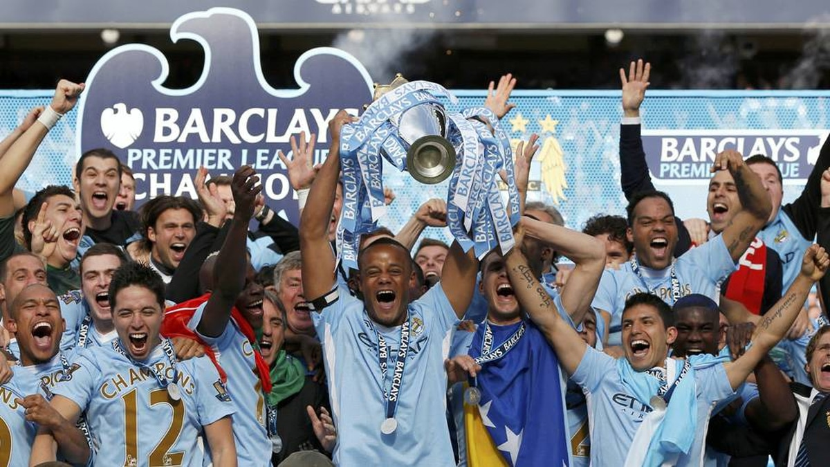 Manchester City captain Vincent Kompany lifts the English Premier League trophy following their soccer match against Queens Park Rangers at the Etihad Stadium in Manchester, northern England.