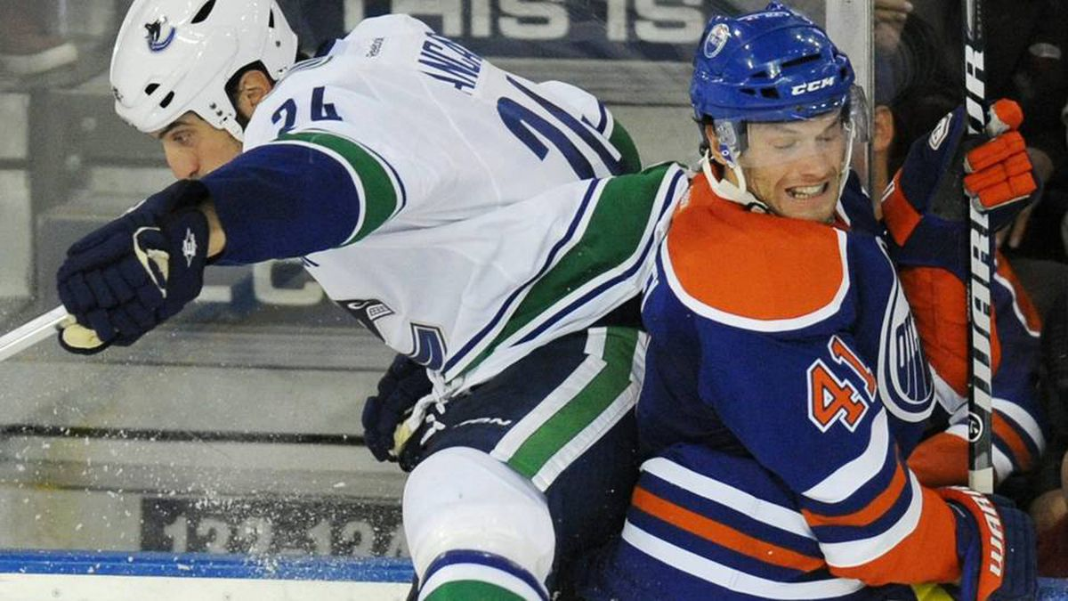 Vancouver Canucks' Mark Mancari, left, checks the Edmonton Oilers' Taylor Chorney during second period NHL preseason hockey action in Edmonton on Thursday, September 22.