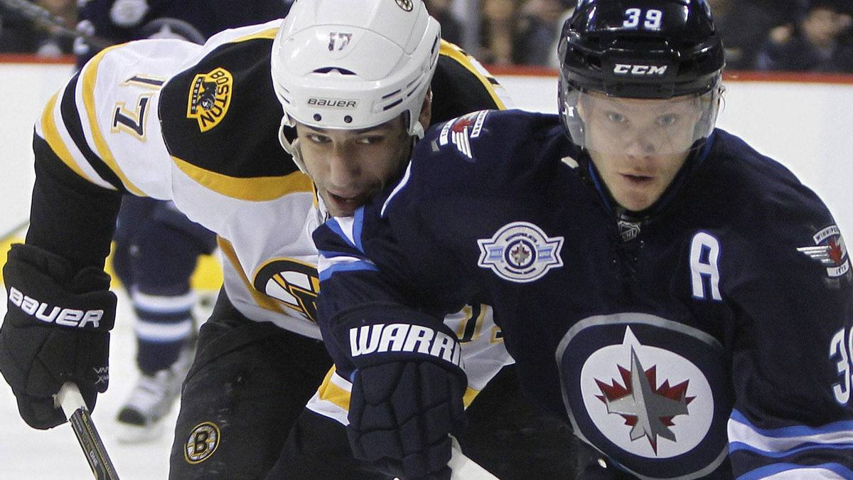 Boston Bruins' Milan Lucic (17) and Winnipeg Jets' Tobias Enstrom (39) battle for the puck during first period NHL hockey action in Winnipeg, Friday, February 17, 2012. THE CANADIAN PRESS/Trevor Hagan