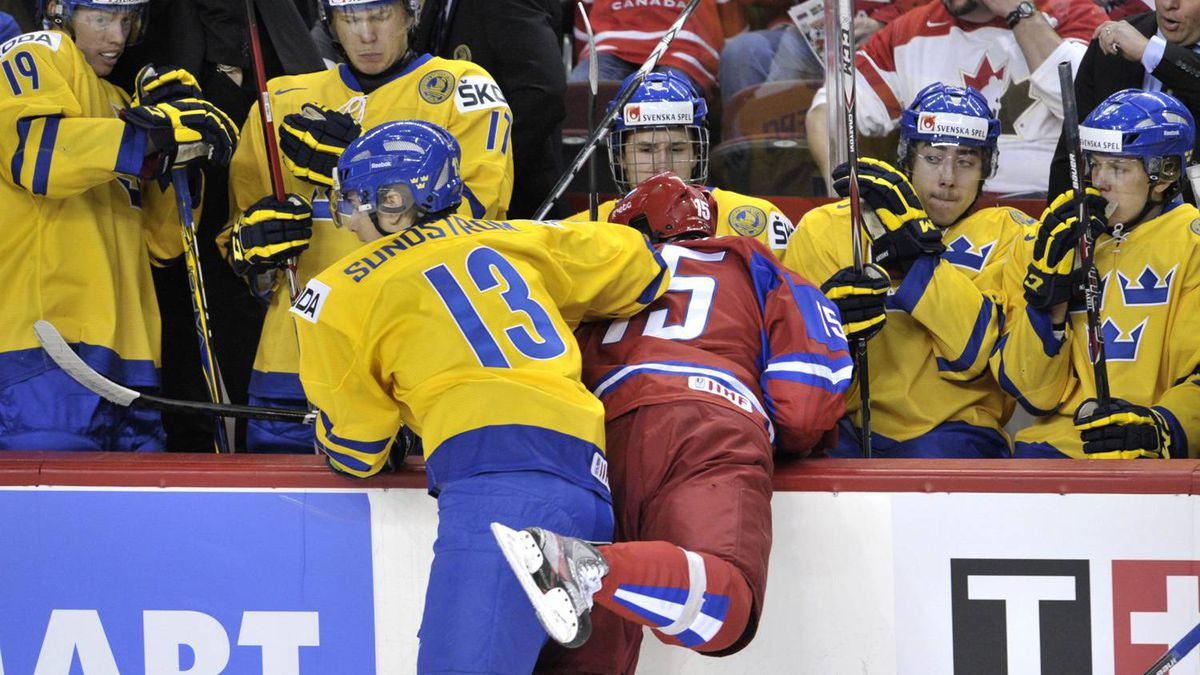 Sweden's Johan Sundström hammers Pavel Kulikov into the Swedish bench during the first period.