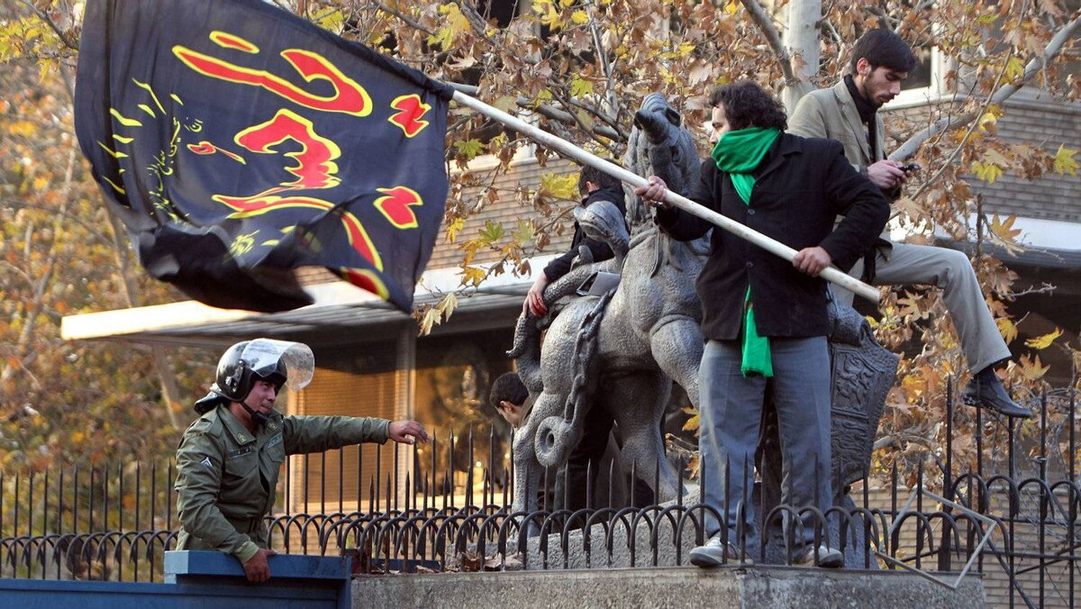 """Iranian protesters (R) wave a flag that reads """"Oh Hussein"""", refering to the grandson of Prophet Mohammed, as they stand on the wall of the British embassy in Tehran on November 29, 2011."""
