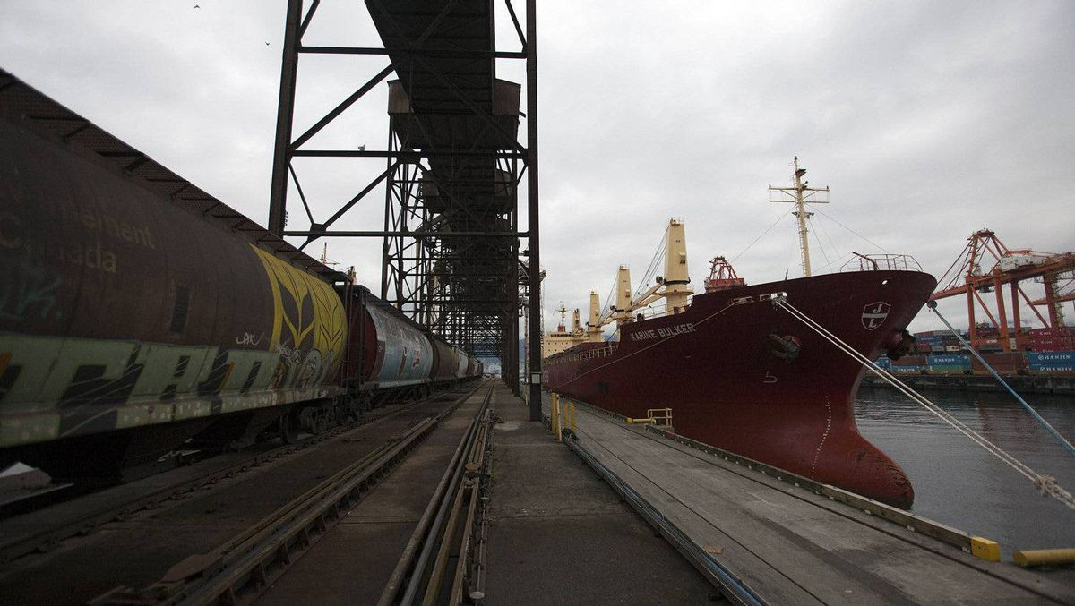 A wheat train pulls up next to a cargo ship at the Alliance Grain Terminal in Vancouver