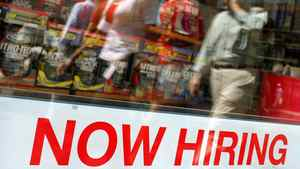 """Pedestrians walk past a """"Now Hiring"""" sign in the window of a GNC shop in Boston, Massachusetts in this file image."""