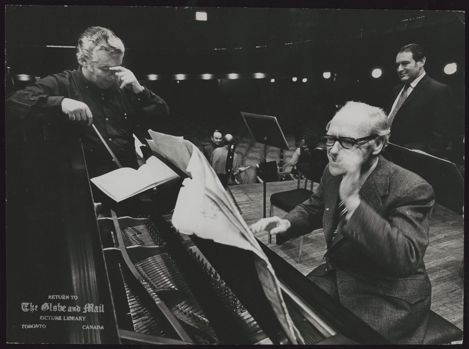 Mitchell SHARP Toronto. Politician Conductor Victor Feldbrill ponders his fate as he rehearses an exuberant Mitchell Sharp for the External Affairs Minister's world concert debut at Massey Hall last night. Mr. Sharp selected Mozart's Piano Concerto - No. 21 (andante). Also making his, concert debut was Donald S. Macdonald, Minister of Energy, Mines and Resources, who conducted the Toronto Symphony Orchestra in a rendition of the Colonel Bogey march. The guests were taking part in a Christmas concert.