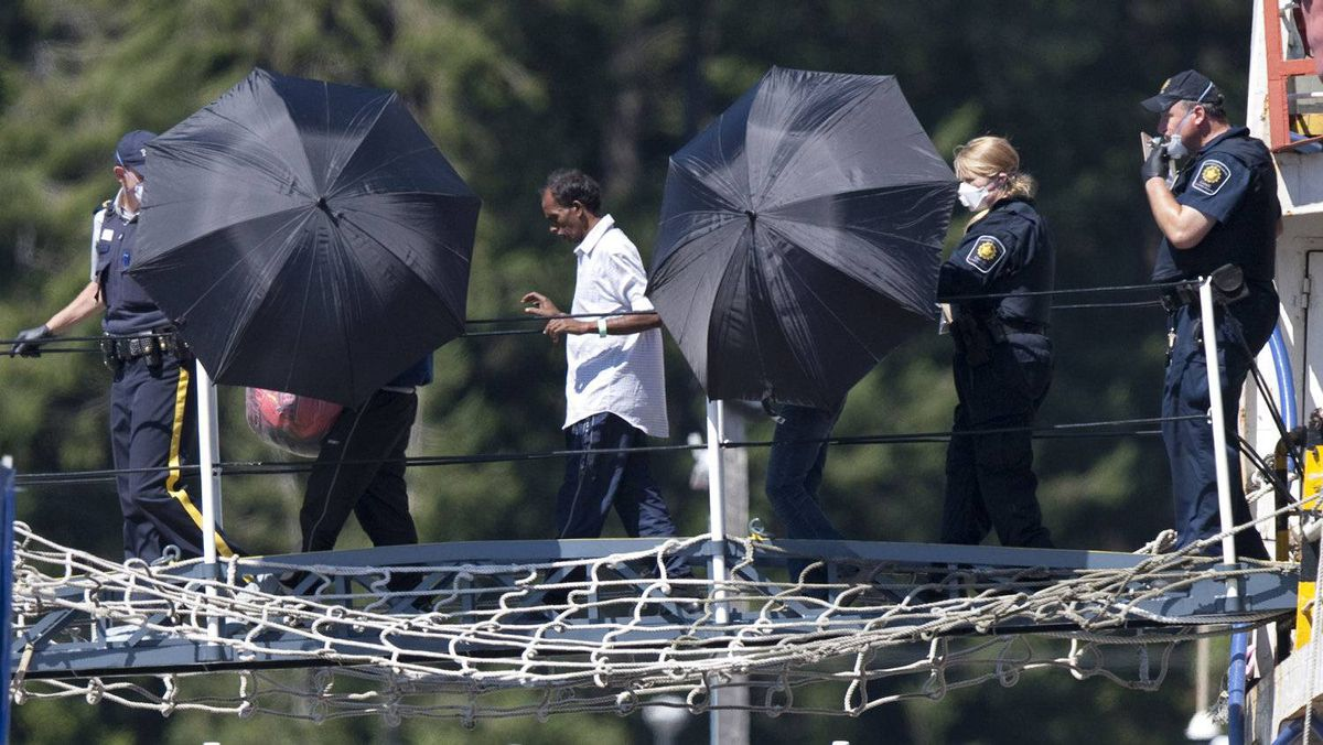 Tamils from Sri Lanka are escorted off the MV Sun Sea by RCMP and Canada Border Services officers at Canadian Forces Base Esquimalt near Victoria on Aug. 13, 2010.