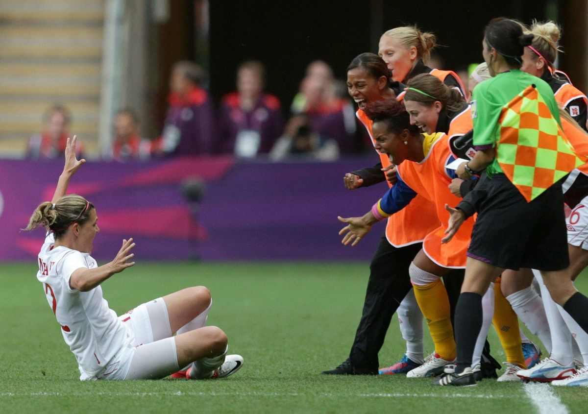 Christine Sinclair, left, slides towards her teammates while celebrating after scoring their second goal against Britain.