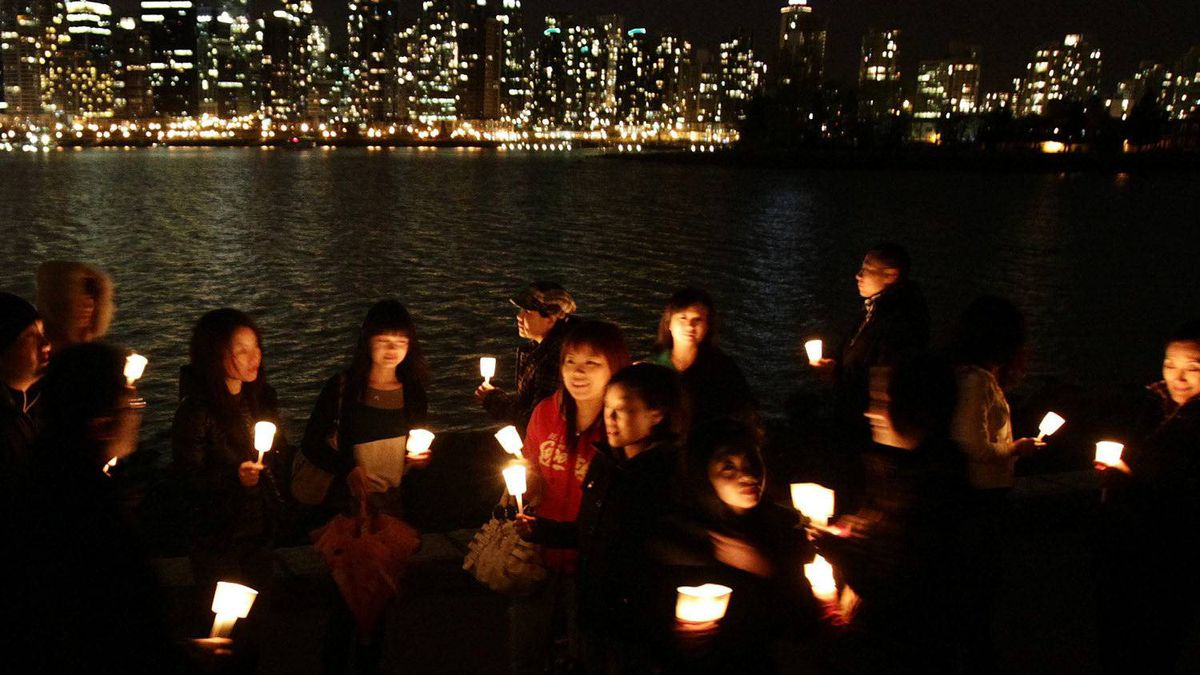 A group of friends hold candles as they gather along the Stanley Park seawall to mark Earth Hour in Vancouver, B.C., on Saturday March 27, 2010 to bring awareness to climate change.
