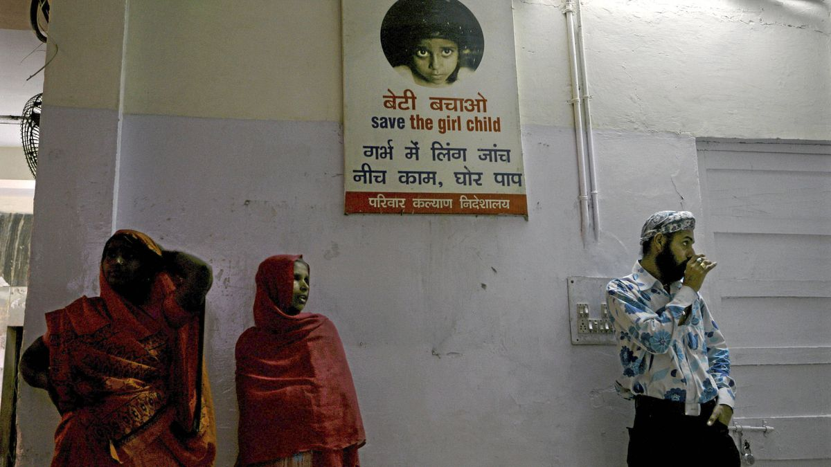 """Indian visitors stand next to a poster which reads """"save the girl child, finding out the gender of a foetus is a sin"""" at a hospital in New Delhi on March 6, 2008. The Indian government says it wants to change the mindset against girls by giving cash incentives to their families to dissuade them from aborting female foetuses."""