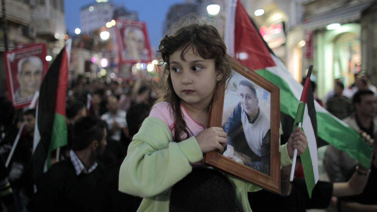 A girl holds a portrait of a Palestinian held in an Israeli jail during celebrations after a deal to end a prisoners hunger strike was agreed, in the West Bank city of Ramallah May 14, 2012.