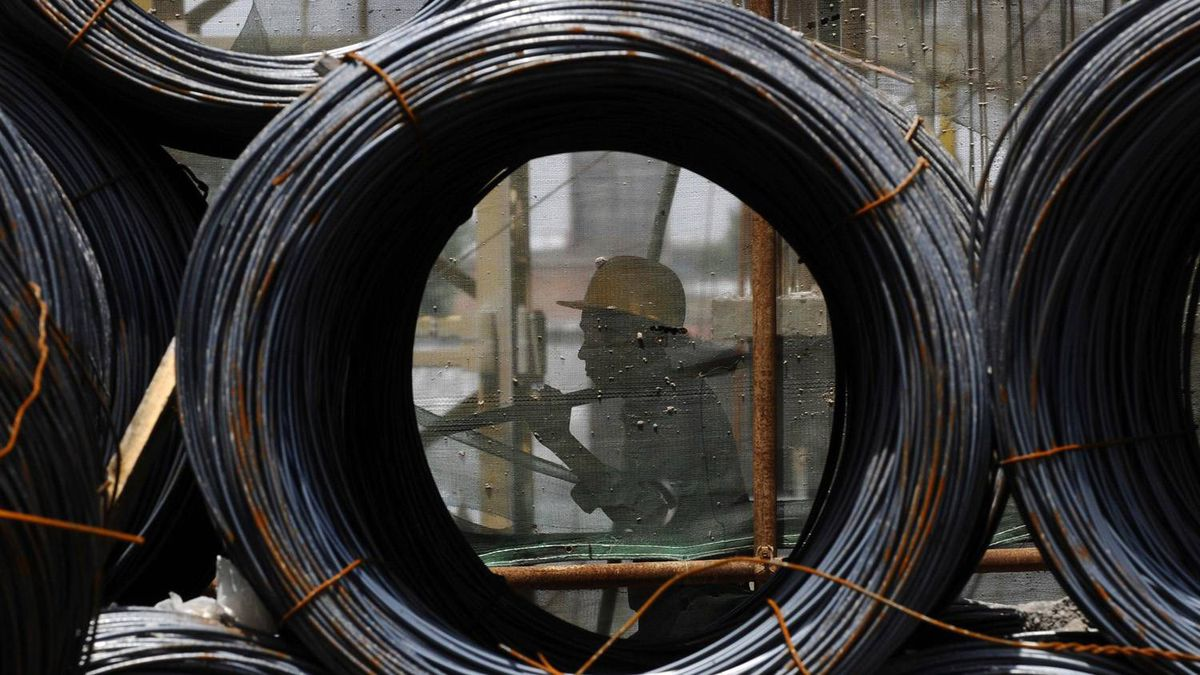A worker walks past steel wire rod coils at a construction site in China