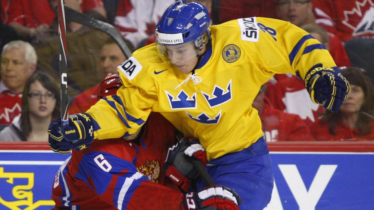 Sweden's Erik Thorell and Russia's Mikhail Naumenkov fight for control of the puck during the first period.