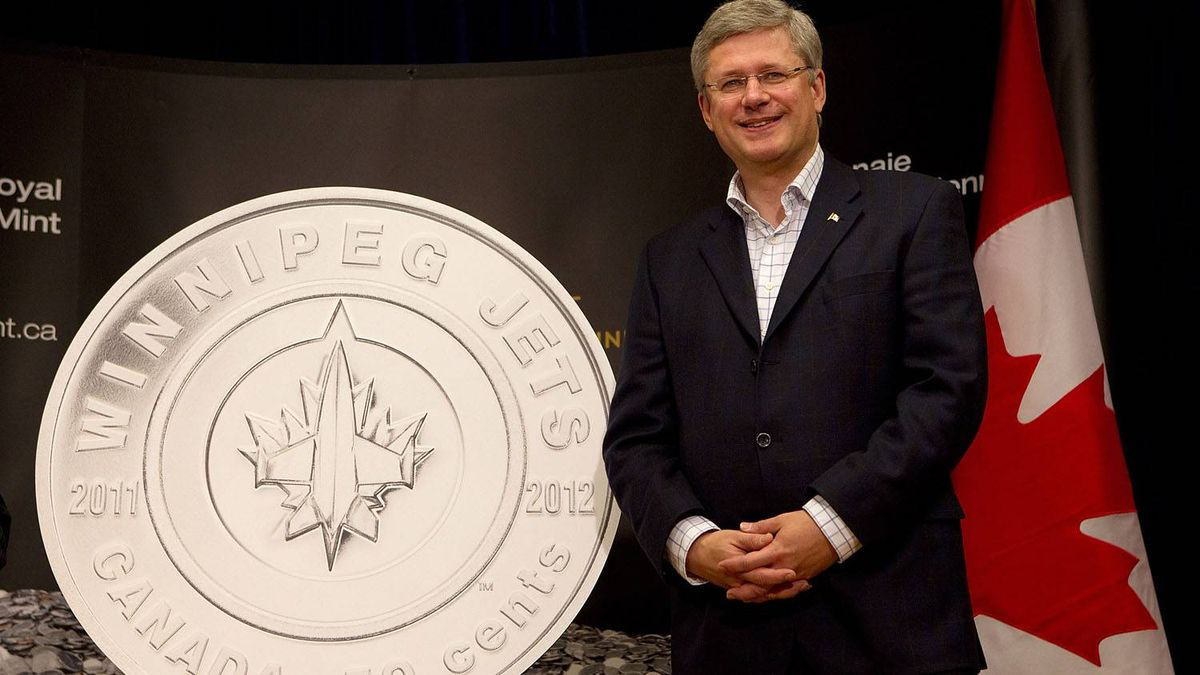 Canada's Prime Minister Stephen Harper stands beside a commemorative coin unveiled at the MTS Centre beore the Winnipeg Jets and Montreal Canadiens game at the MTS Centre on October 9, 2011 in Winnipeg, Manitoba, Canada. The game is Winnipeg's first NHL regular season game in 15 years.