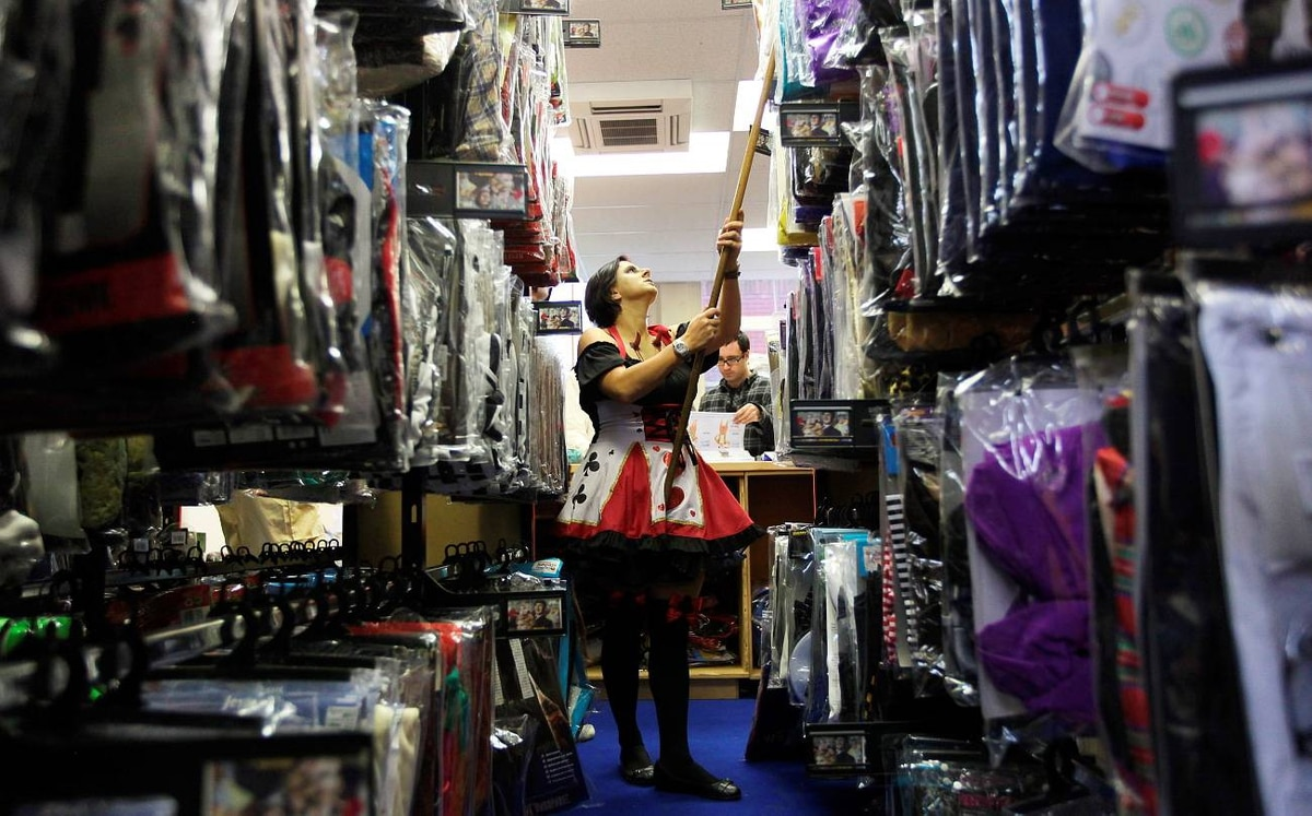 An employee of Angels Costumiers looks in the stock room for costumes for customers.