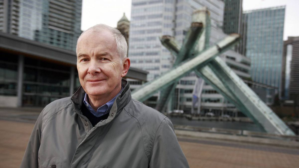 John Furlong stands beside the 2010 cauldron in Vancouver, B.C.