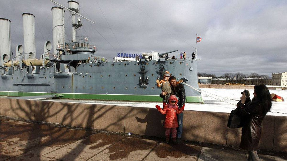 People pose for a picture in front of the cruiser Aurora in St. Petersburg, Russia, March 3, 2012. The cruiser is a popular tourist attraction famous for its role in the 1917 Bolshevik revolution.