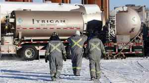 Trican Well Service employees walk toward liquid nitrogen storage tanks at a hydraulic fracturing operation near Bowden, Alta., Tuesday, Feb. 14, 2012.